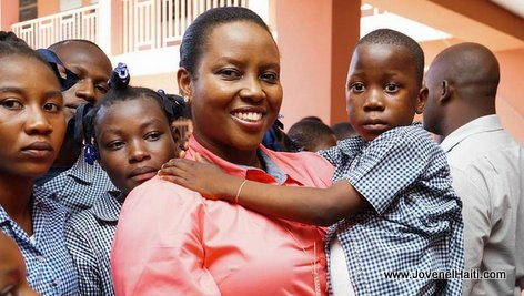 First Lady Martine Moise holding a young Haitian Student