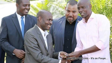Haitian President Jovenel Moise hands over the key to a new vehicle to a city mayor